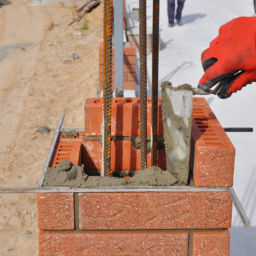 Closeup of a Bricklayer Worker Installing Red Blocks and Caulking Brick Masonry Joints Exterior Wall with Trowel Putty Knife Outdoor. Bricklaying.