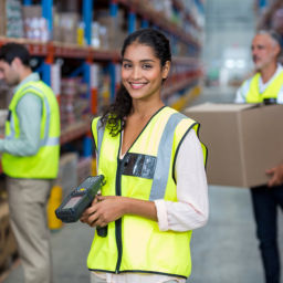 Portrait of female warehouse worker standing with barcode scanner in warehouse