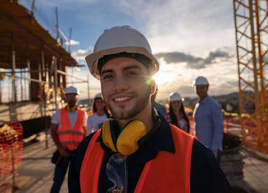Portrait of a happy construction worker at a building site with a group of workers at the background
