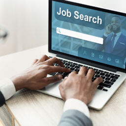 Employment Concept. Back view over the shoulder of black man using laptop with job search engine on screen, typing